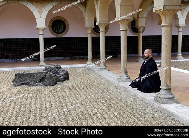 Zen buddhist monk practising zazen (meditation) in Orval trappist abbey's zen garden, Belgium