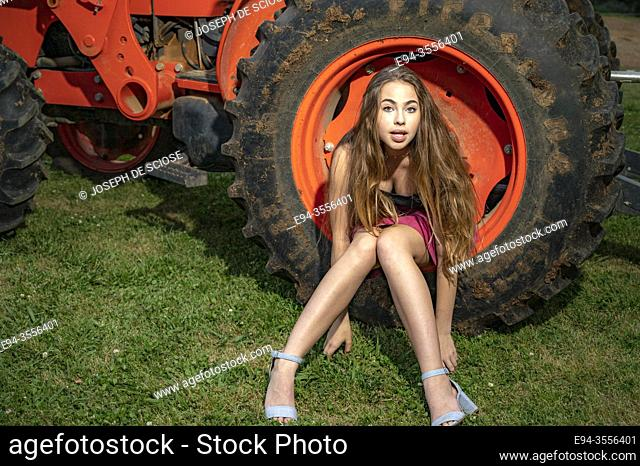 A 14 year old brunette girl sitting on the wheel rim of a farm tractor