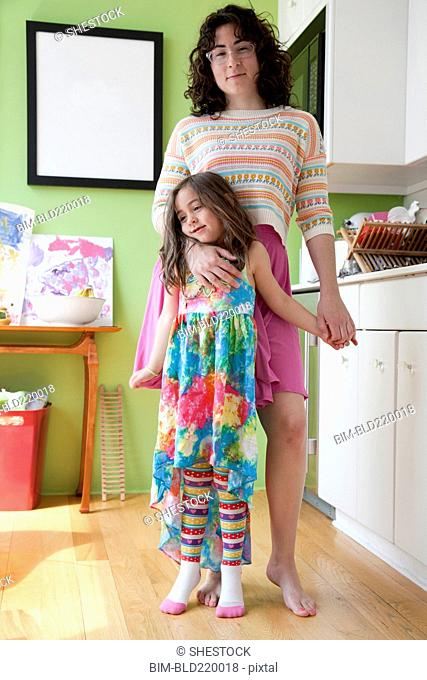 Caucasian mother and daughter hugging in kitchen