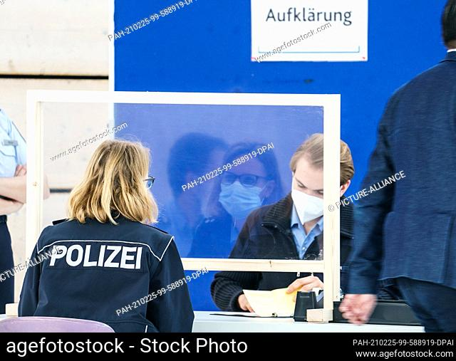 25 February 2021, Rhineland-Palatinate, Mainz: A police officer (l) conducts a pre-vaccination educational session with AstraZeneca vaccine at a police...