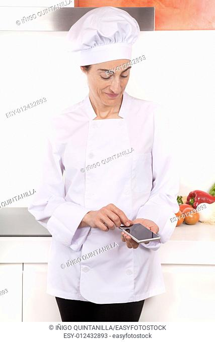 portrait of brunette happy chef woman with professional jacket and hat in white and orange kitchen using blank screen mobile phone