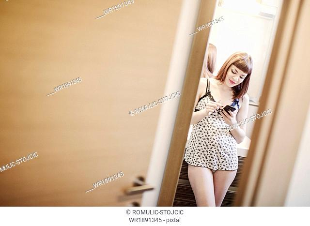 Young woman in nightie text messaging with smart phone