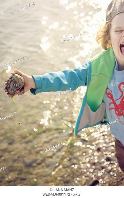 Germany, Mecklenburg-Western Pomerania, Ruegen, Screaming boy holding stone at the coast