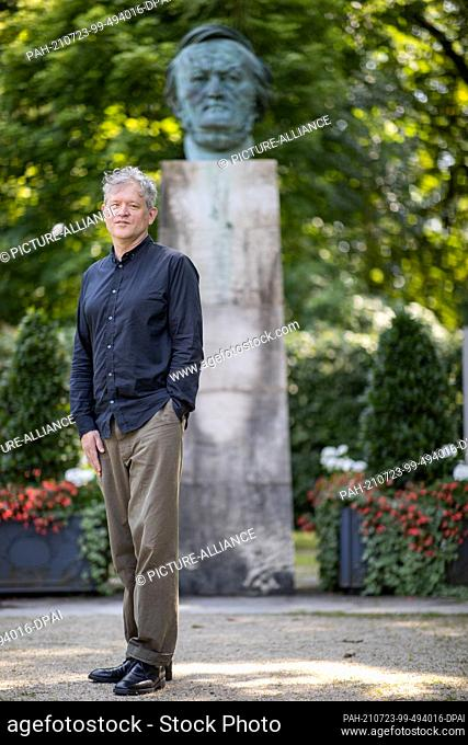 """23 July 2021, Bavaria, Bayreuth: US director Jay Scheib stands in front of a bust of Richard Wagner. Scheib is showing """"""""Siegfried's"""""""" dragon fight in virtual..."""