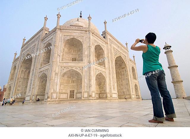 Woman photographing the Taj Mahal at dawn