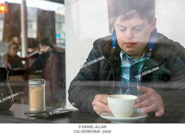 Man with down syndrome having coffee by cafe window