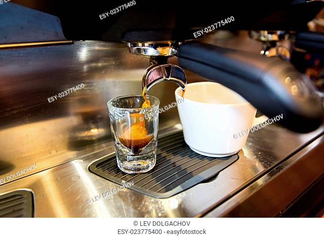 equipment, drinks and technology concept - close up of espresso machine making coffee