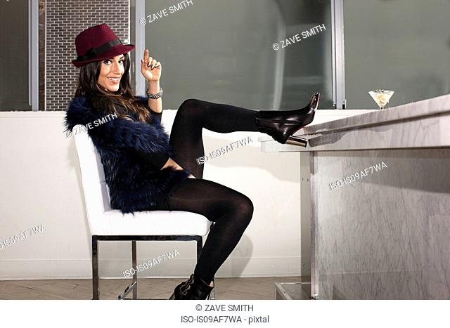 Portrait of mid adult woman in with feet up in cocktail bar
