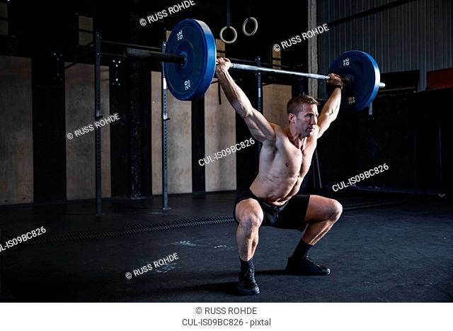 Man exercising in gym, using barbell, front squat position