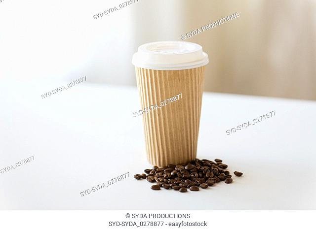 close up cup and roasted coffee beans on table