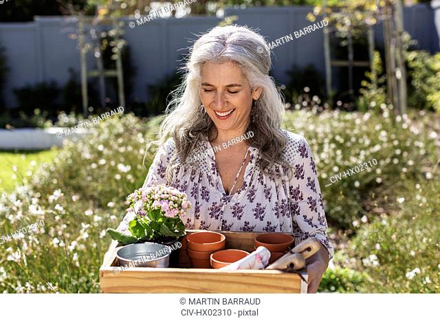 Smiling mature woman carrying gardening tray in sunny garden