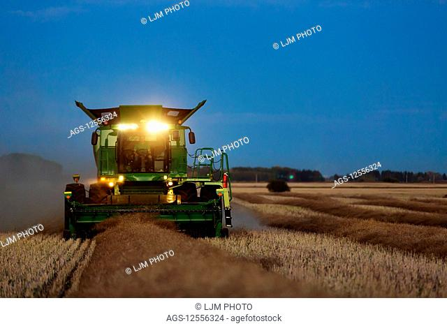 A combine with its lights on harvesting canola after sunset; Legal, Alberta, Canada