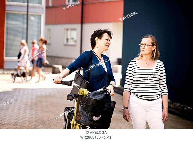 Thoughtful mature woman with bicycle while talking with female friend on footpath in city