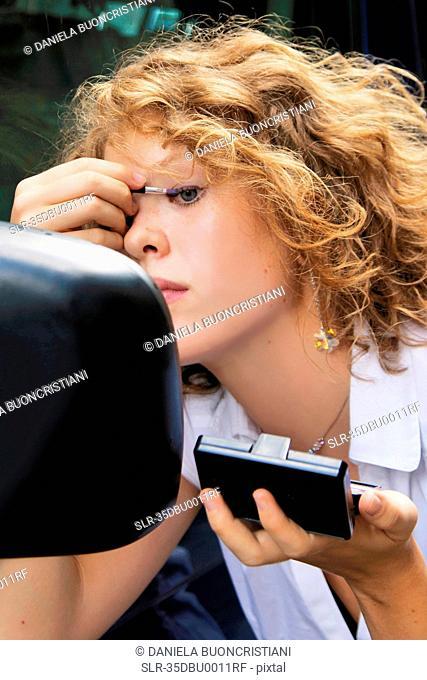 Woman applying makeup in car mirror
