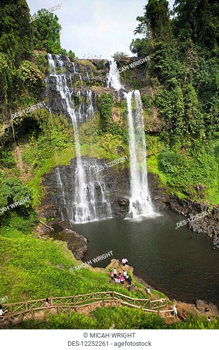A group of travelers gather to play in the Tad Yuang Waterfall on the Bolaven Plateau; Laos