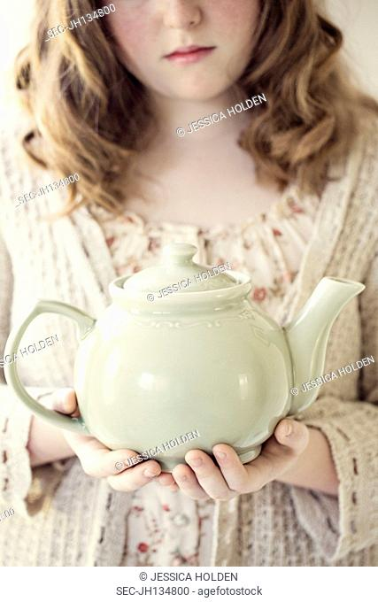 Picture of girl (13-15) holding teapot