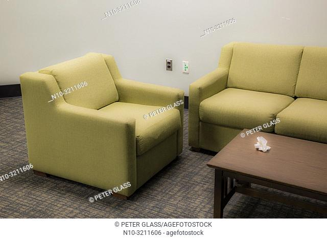 Sofa, chair, and a table, with crumpled paper on it, in a business office lobby