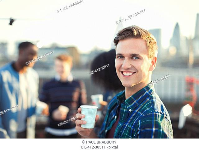 Portrait smiling young man drinking at rooftop party