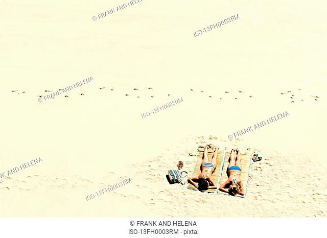 Two girls sunbathing on sandy beach
