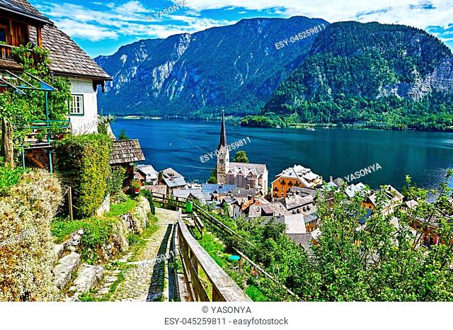 Hallstatt Austria vintage architecture and old houses in picturesque austrian mountains Alps on lake Hallstattersee. Paved stone walking track among green trees