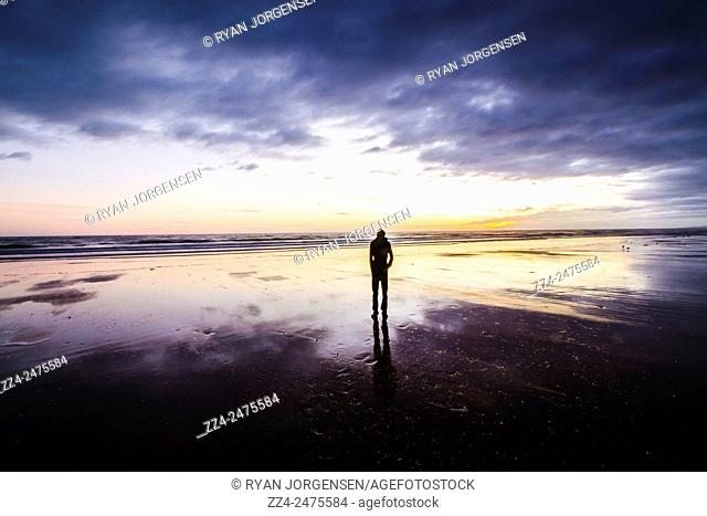 Beautiful beach sunrise with the silhouette of a man watching the dawn of a new day. Ulverstone Beach, Tasmania, Australia