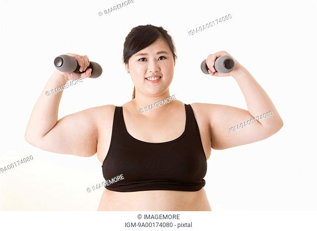 Young woman holding dumbbell and smiling at the camera