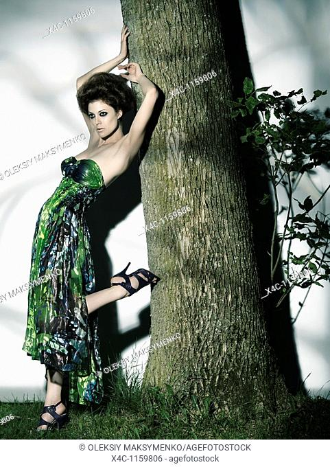 High fashion photo of a beautiful woman in elegant dress leaning against a tree trunk