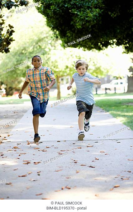 Boys running on sidewalk