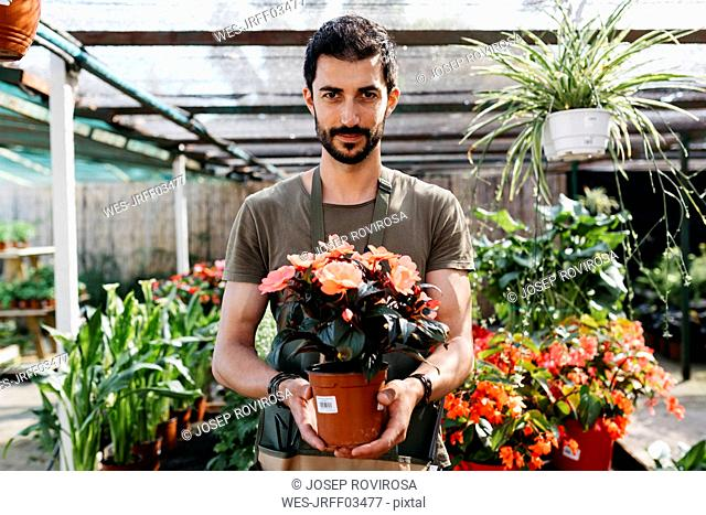 Portrait of a gardener in a garden center holding flower