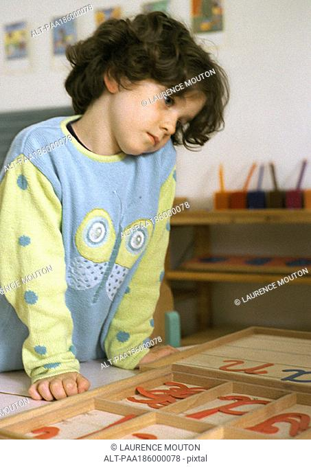 Child looking at plastic letters