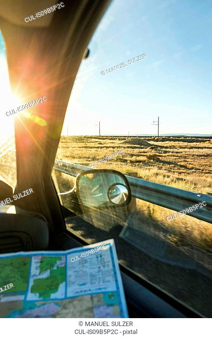 Wing mirror view of man with map on the road in sunlight, Arizona, USA