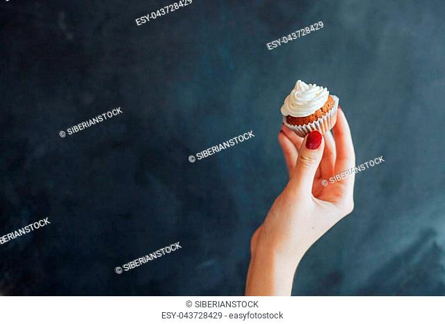 Woman holding a chocolate muffin on black background