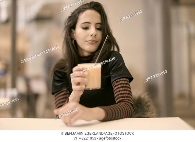 portrait of sensitive woman holding healthy juice glass while enjoying break at table in café, in Munich, Germany