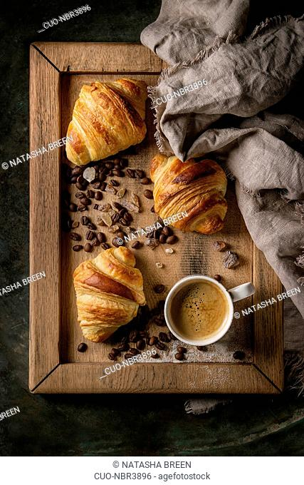 Fresh baked traditional croissants on linen textile with mug of espresso coffee, coffee beans and sugar on wooden tray over dark metal background