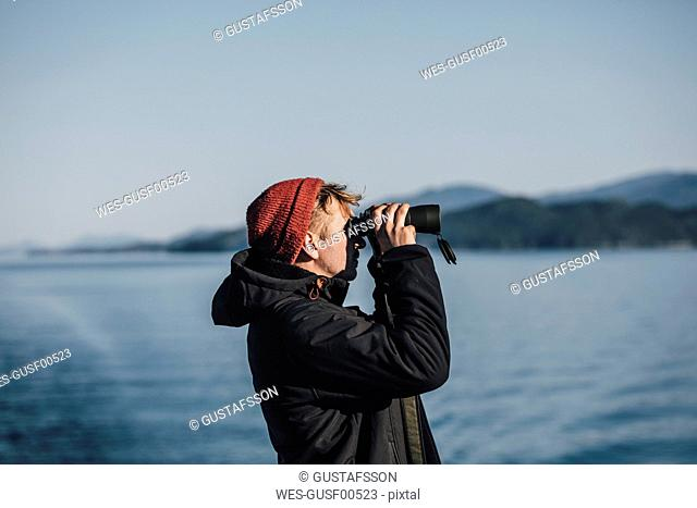 Canada, British Columbia, man looking through binoculars at the coast