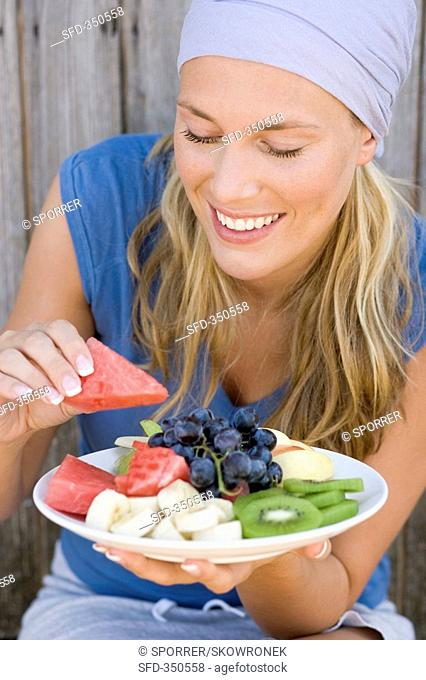Woman eating watermelon from a plate of fruit
