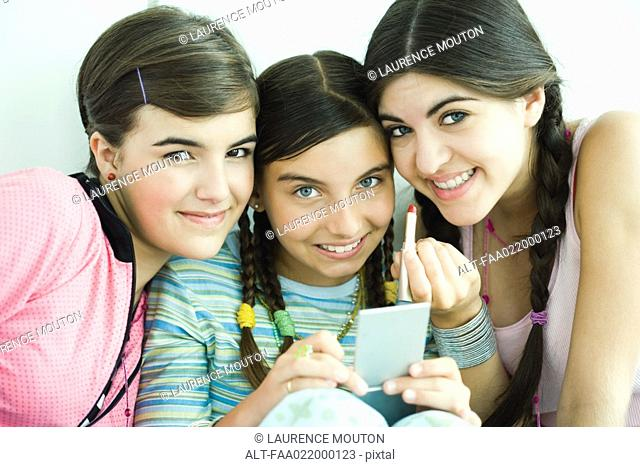 Three young female friends holding make-up, smiling at camera
