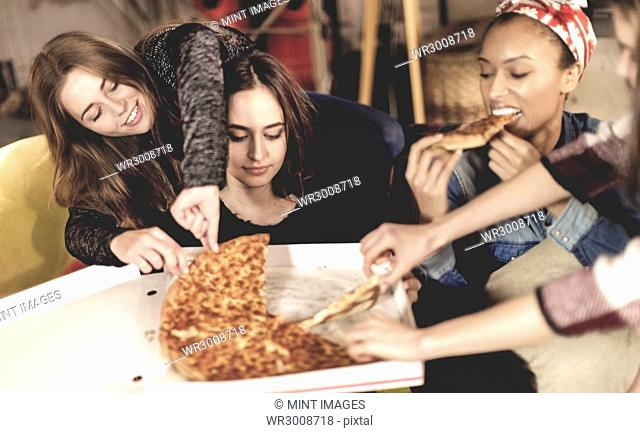 Four young women sitting round a table, eating pizza
