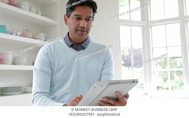 Asian Indian man sitting at kitchen counter using digital tablet.Shot on Canon 5d Mk2 with a frame rate of 25fps