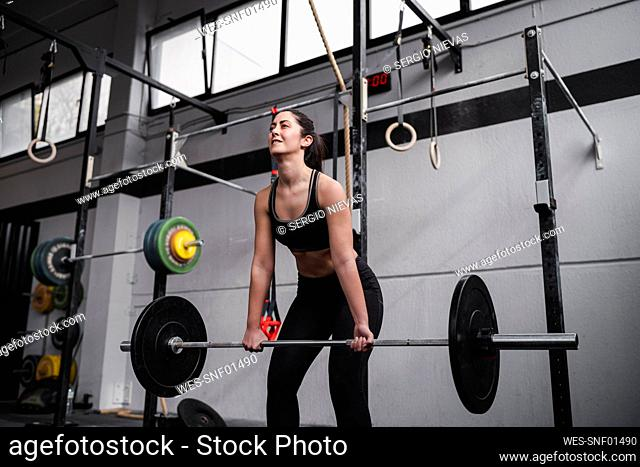 Active woman lifting weight in gym