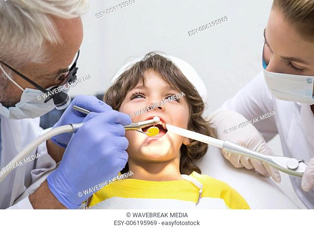 Pediatric dentist and assistant examining a little boys teeth