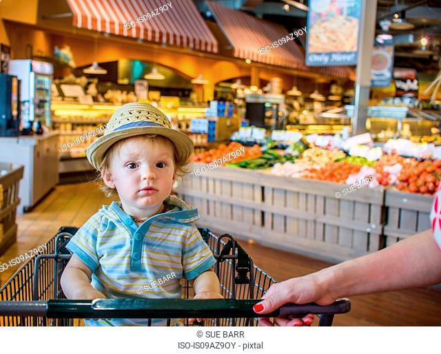 Baby boy wearing straw hat sitting in shopping trolley