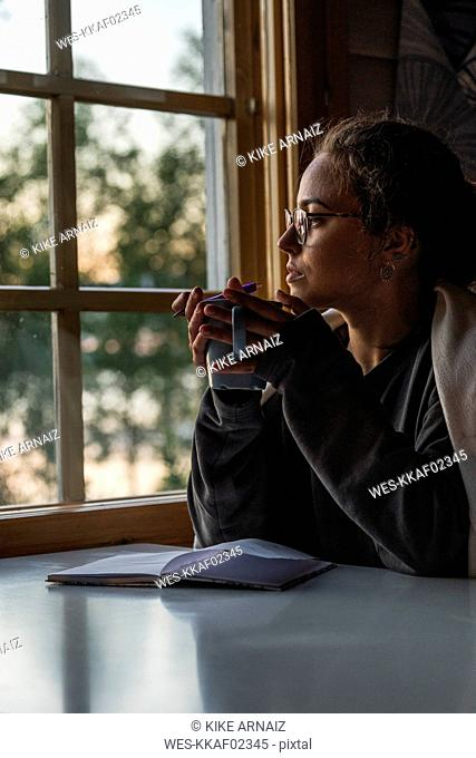 Finland, Lapland, young woman sitting at the window holding a mug