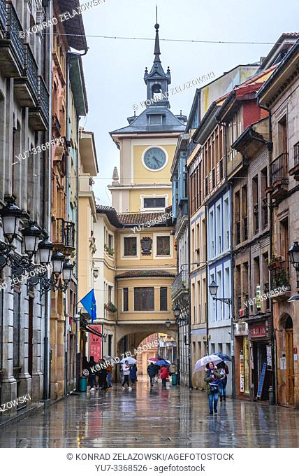 Buildings on Calle Cimadevilla - a street in Oviedo in Asturias region of Spain, view with tower of City Hall building