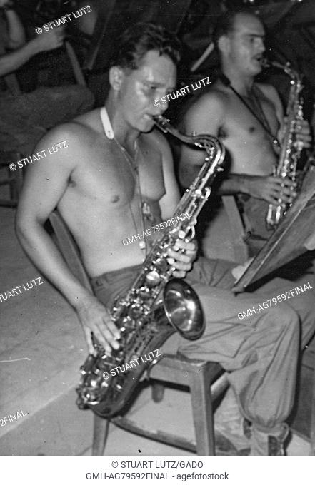 A photograph of two shirtless United States Army servicemen playing saxophones while seated and reading from sheet music