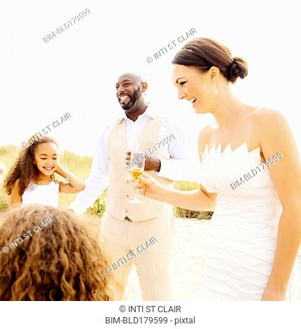 Bride and groom celebrating with flower girl daughters