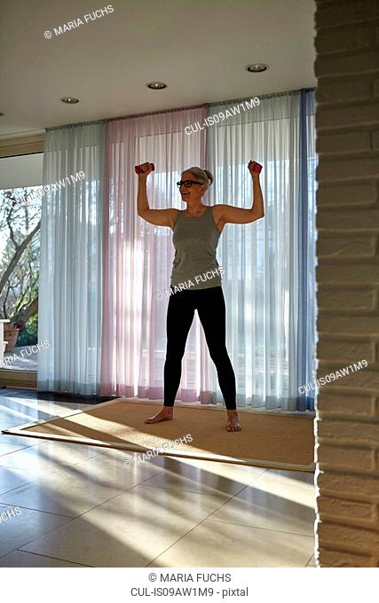 Mature woman exercising with dumbbells in front of patio doors