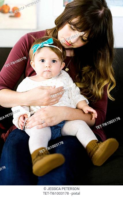 Mother with daughter (12-17 months) sitting on sofa