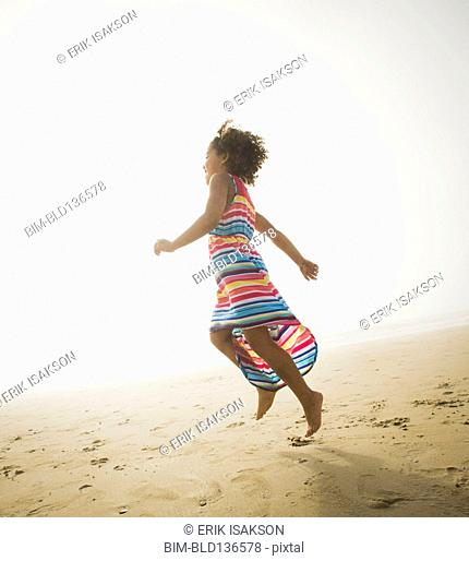 Black girl playing on beach
