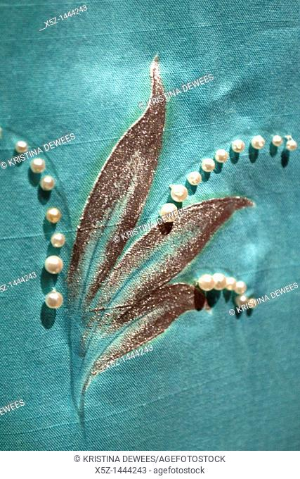 A beaded and embroidered detail on a blue dress